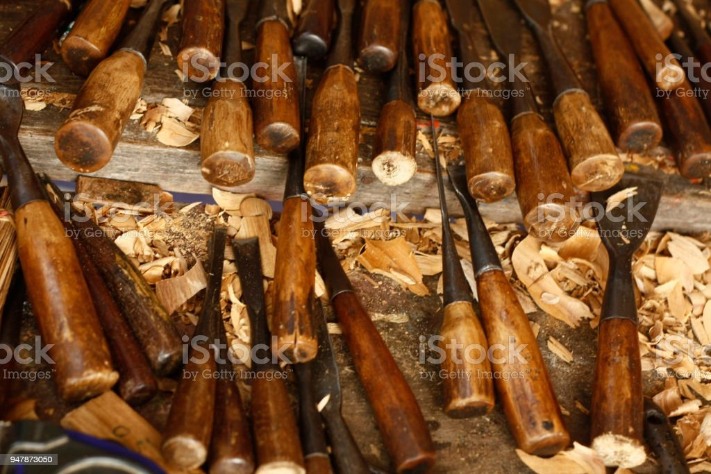 Different sized and varying shaped hardwood carving chisels and tools in a woodworkers workshop covered in wood shavings stock photo