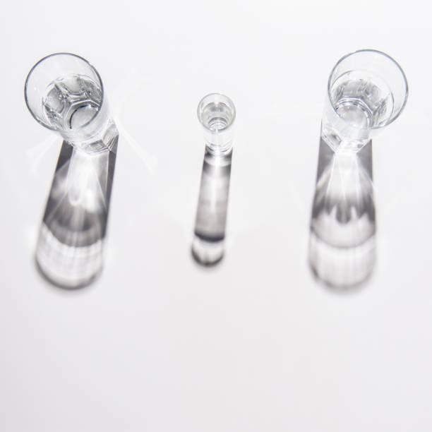 異なるサイズの白いテーブルに水とグラス ストックフォト