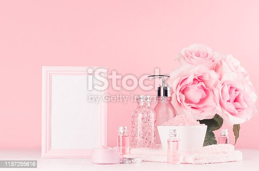 1056636898 istock photo Different skin care products with romantic roses bouquet and blank frame for text on girlish elegant pink pastel background with copy space. 1137255616