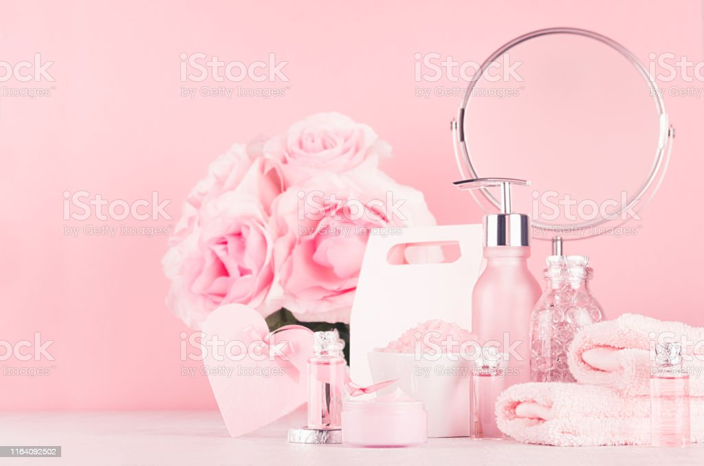Different skin care products with romantic roses bouquet, round...