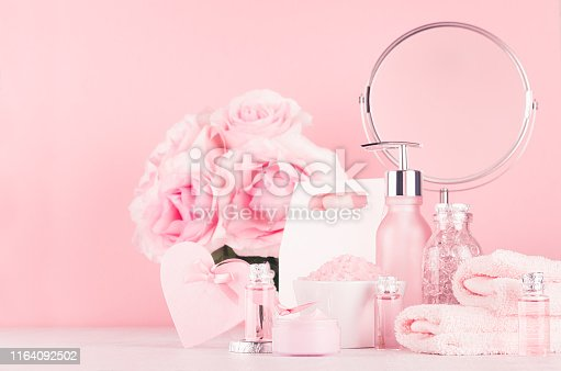 1056636898 istock photo Different skin care products with romantic roses bouquet, round mirror on girlish elegant pink pastel background. 1164092502