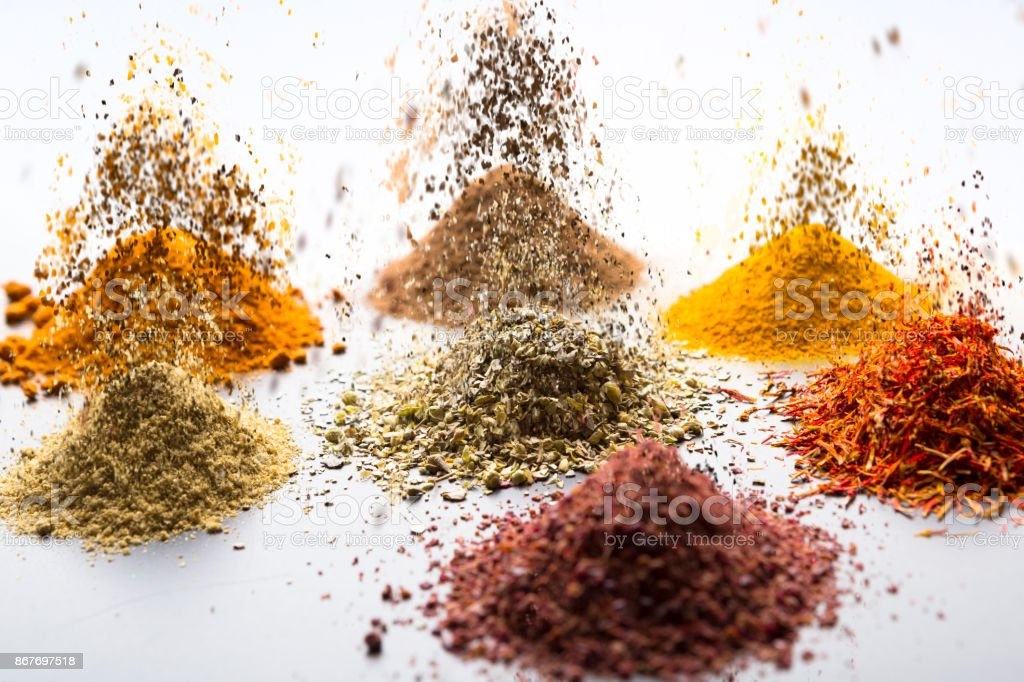 Different spices scattered on reflective surface falling from above stock photo