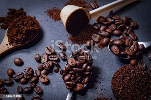 Different spoons filled with roasted coffee beans of with grinded coffee on a slate stone platter background. On the slate stone an arrangement of loose roasted coffee beans and grinded coffee is complementing the whole scenery.