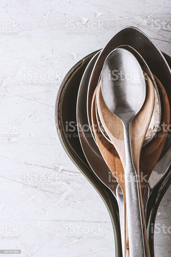 Different spoons on the  white table vertical stock photo