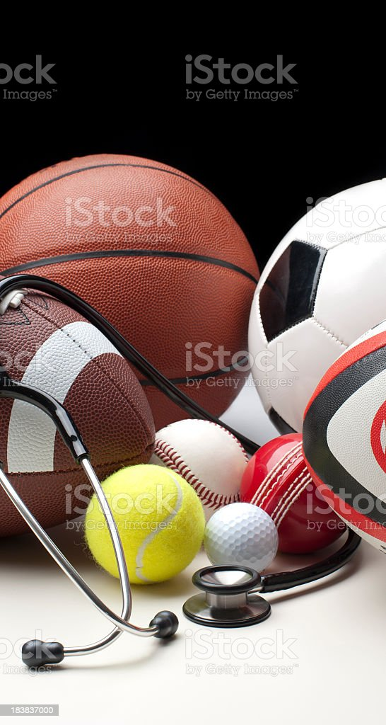 Different sports balls with stethoscope royalty-free stock photo