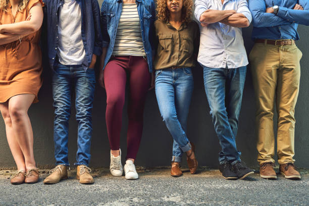 Different styles forming as one Shot of a group unrecognizable people leaning against a wall while posing for a photo outside cross legged stock pictures, royalty-free photos & images