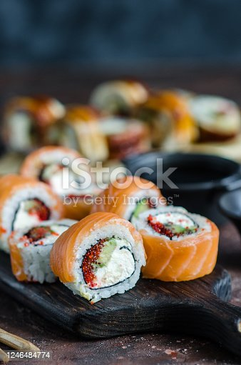 Different Sushi rolls with red fish and eel, wasabi and ginger on a plate on wooden background.