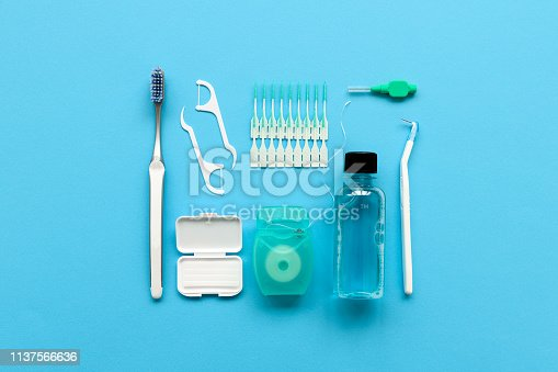 Different tools for dental care on blue background. Toothbrush, cleanser, floss, flossers, wax for braces and  interdental brush. Top view. Flat lay. Dental hygiene and care concept