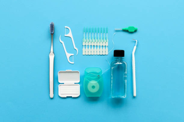 different tools for dental care on blue background. toothbrush, cleanser, floss, flossers, wax for braces and  interdental brush. top view. flat lay. dental hygiene and care concept - przybory toaletowe zdjęcia i obrazy z banku zdjęć