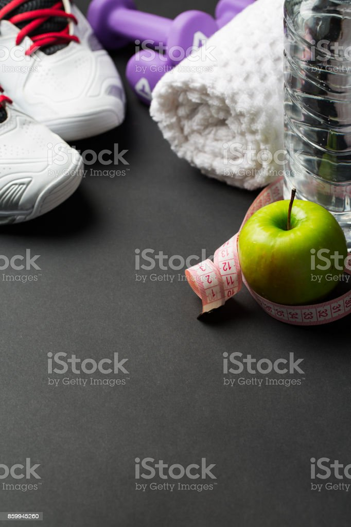 Sport shoes, pair of dumbbells, green apple, measuring tape and...