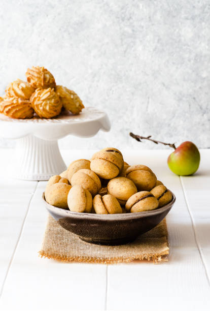 Different type of delicious cookies and a apple on white wooden table - foto stock
