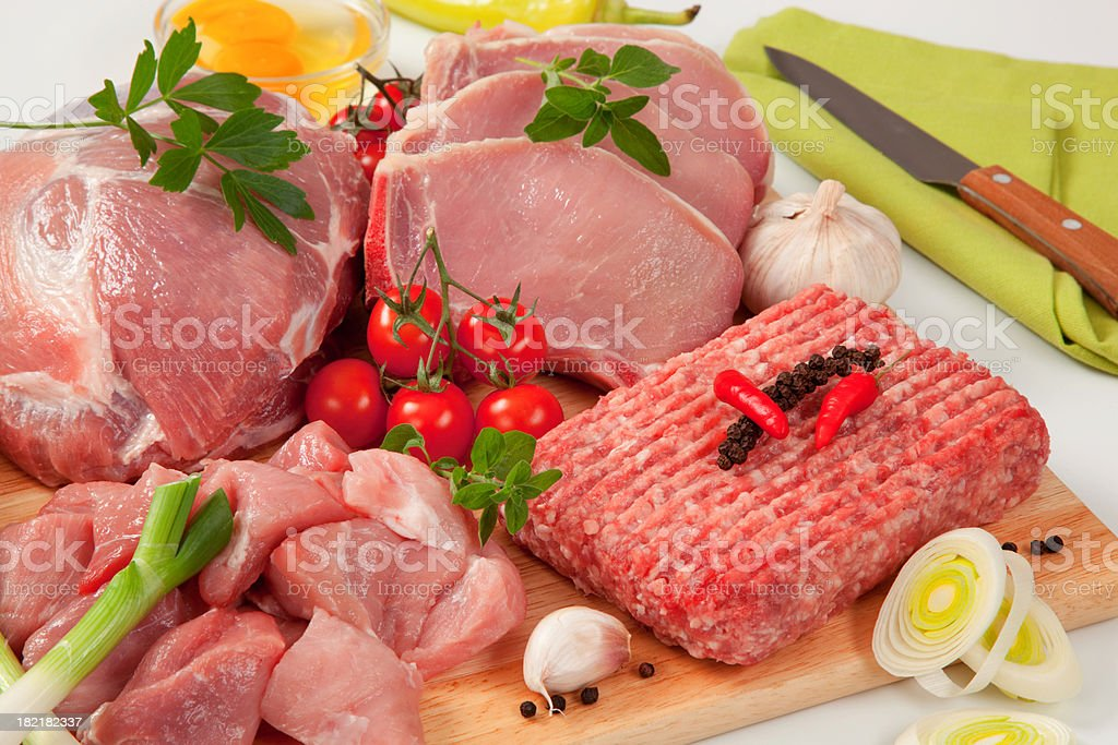 Different type of raw meat on a chopping board, garnished royalty-free stock photo