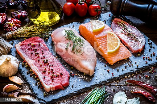 High angle view of four different types of animal protein like a raw beef steak, a raw chicken breast, a raw salmon fillet and a raw pork steak on a stone tray surrounded by condiments, spices and vegetables. Low key DSLR photo taken with Canon EOS 6D Mark II and Canon EF 24-105 mm f/4L