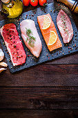Top view of four different types of animal protein like a raw beef steak, a raw chicken breast, a raw salmon fillet and a raw pork steak on a stone tray surrounded by condiments, spices and vegetables. The stone tray is at the top of the image and at the opposite side is a useful  copy space on a dark brown rustic wooden background. Low key DSLR photo taken with Canon EOS 6D Mark II and Canon EF 24-105 mm f/4L