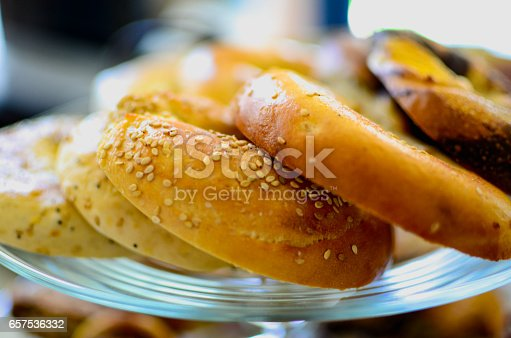 Sesame, everything, plain and more bagles. They're cut in to halfs and arranged on a plate.