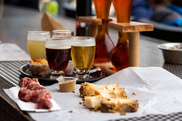 Different types of beer like coconut and cherry beer and cheese with smocked sausage stock photo