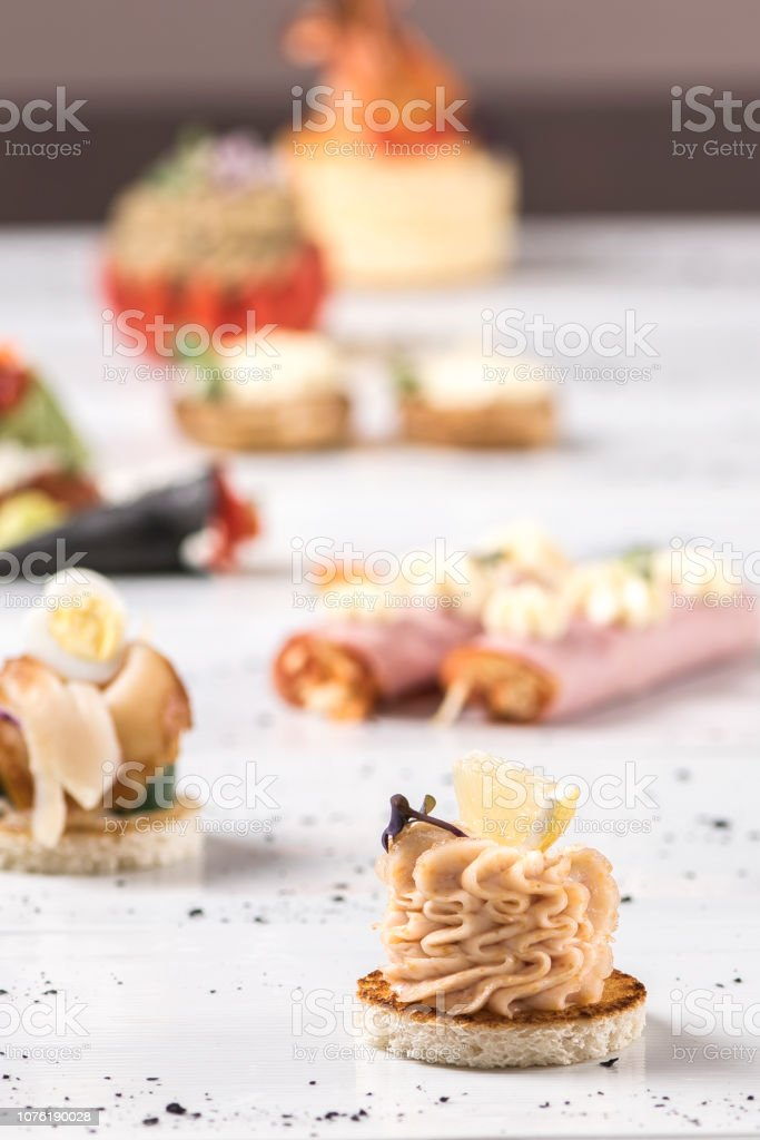 Different types of canapes,  placed on individual plates,  finger food,  dark background stock photo