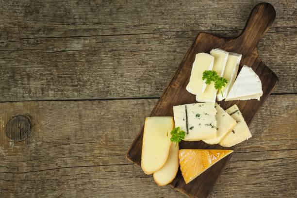 Different types of cheese on a wooden cutting board. stock photo