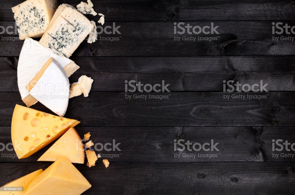 Different types of cheese on black wooden table. Top view stock photo