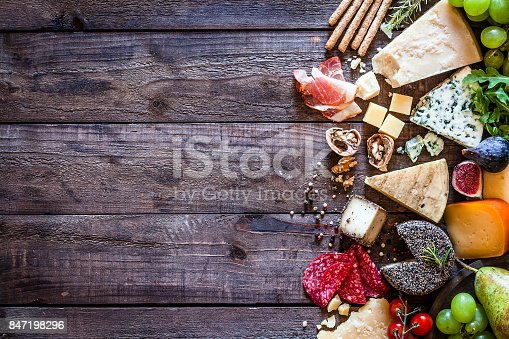 Top view of different types of cheeses and cold meat assortment arranged at the right border of a rustic wooden table leaving useful copy space for text and/or logo. Some fruits like figs and grape and some nuts complete the composition. DSRL studio photo taken with Canon EOS 5D Mk II and Canon EF 100mm f/2.8L Macro IS USM