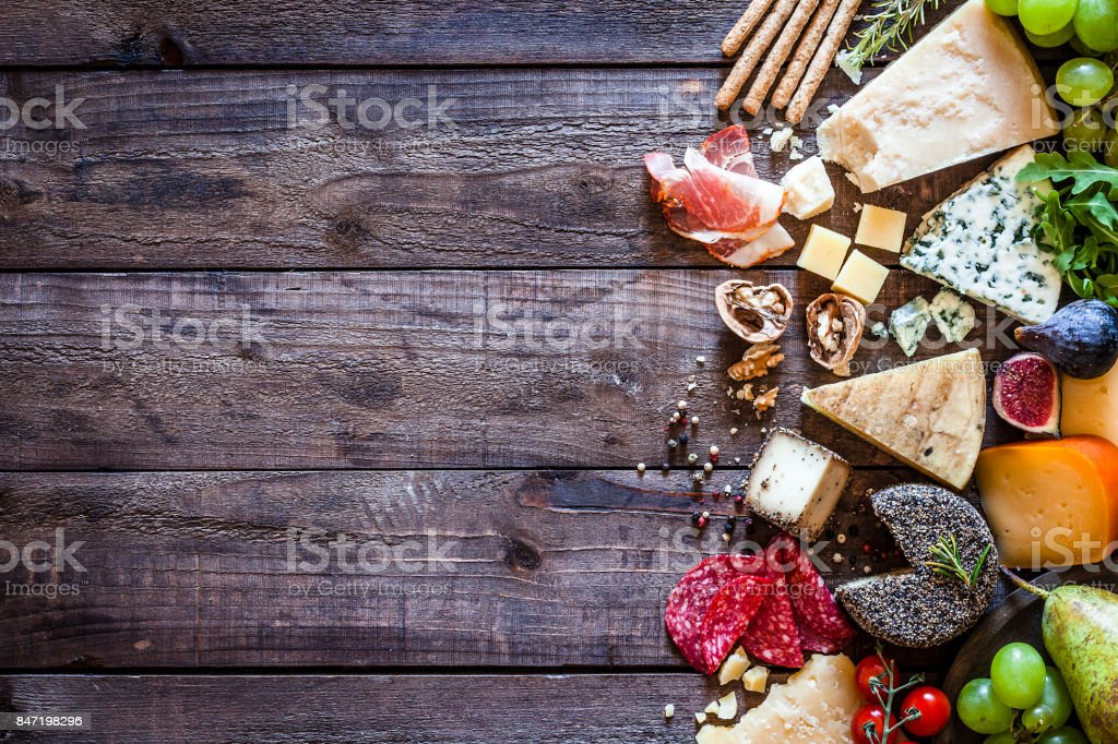 Different types of cheeses on rustic wood table stock photo