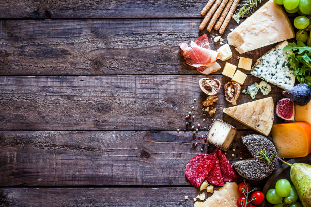different types of cheeses on rustic wood table - formaggio foto e immagini stock