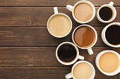 Border of various kinds of coffee in cups of different size on rustic wooden table, top view, copy space