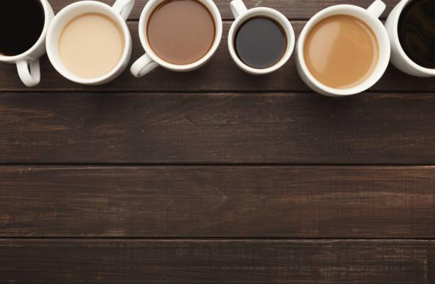 different types of coffee in cups on wooden table, top view - кофейная кружка стоковые фото и изображения