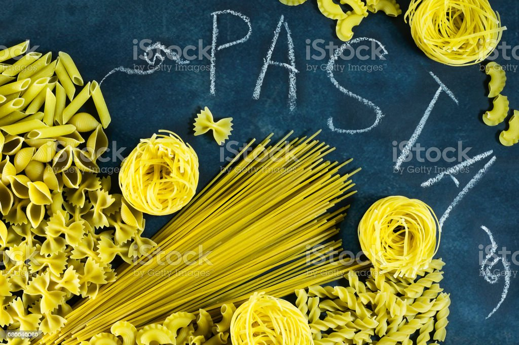 Different types of dried Italian pasta on a blue background. Top view royalty-free stock photo