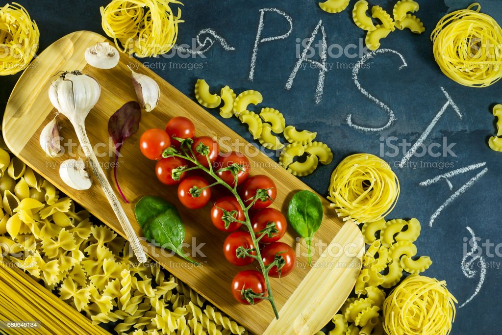 Different types of dried Italian pasta on a blue background. Top view Стоковые фото Стоковая фотография