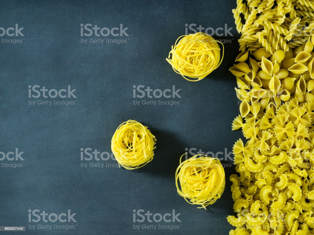 Different types of dry Italian pasta on a dark blue background. foto stock royalty-free