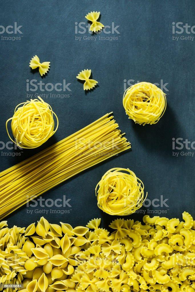 Diferentes tipos de pasta italiana seca sobre un fondo azul oscuro. foto de stock libre de derechos