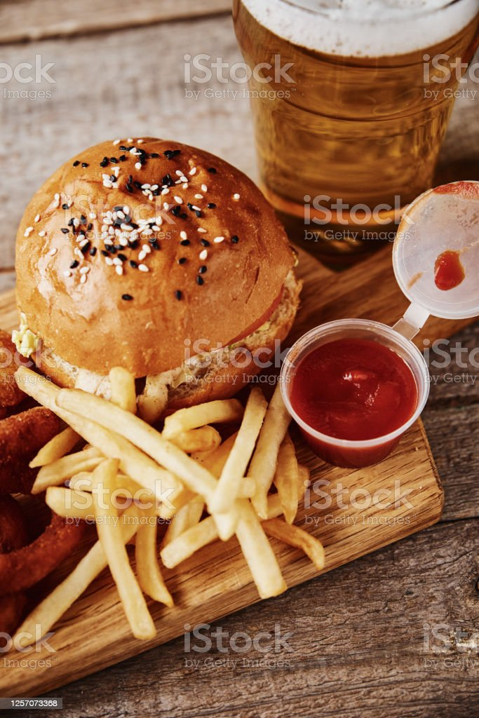 Different Types Of Fastfood And Snacks And Glass Of Beer