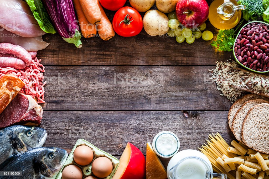 Different types of food making a border on rustic wooden table stock photo