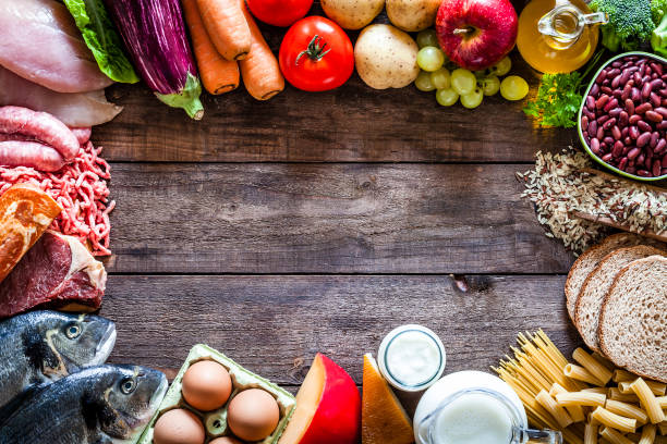 different types of food making a border on rustic wooden table - organic food stock photos and pictures