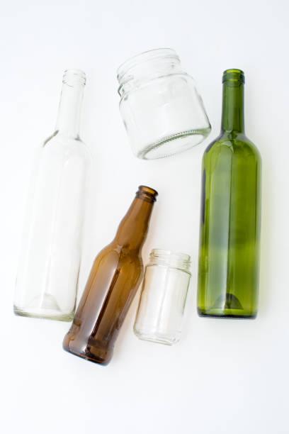 verschiedene arten von glasflaschen auf weißem hintergrund. wiederverwertbare abfälle. recycling, wiederverwendung, müllentsorgung, ressourcen, umwelt und ökologie-konzept. - recycelte weinflaschen stock-fotos und bilder