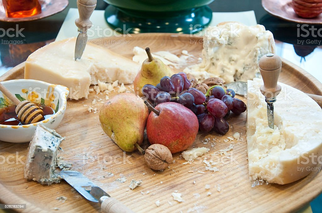 Different types of Italian cheeses served with honey and fruits stock photo