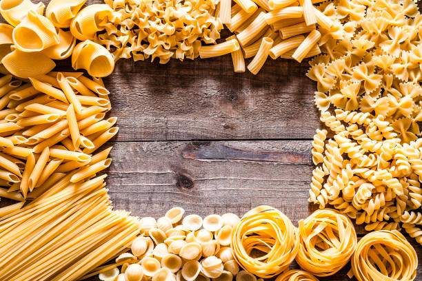Different types of Italian pasta making a frame on rustic wooden table Top view of a rustic wooden table with several types of Italian pasta placed all around the border making frame and leaving useful copy space for text and/or logo at the center. The types of pasta included are spaghetti, orecchiette, conchiglie, rigatoni, fusilli, bow tie pasta, penne and tagliatelle. Predominant colors are yellow and brown. DSRL studio photo taken with Canon EOS 5D Mk II and Canon EF 100mm f/2.8L Macro IS USM uncooked pasta stock pictures, royalty-free photos & images