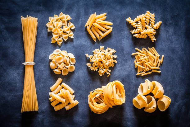 Different types of Italian pasta on black background Top view of several types of Italian pasta arranged into heaps on dark background. The types of pasta included are spaghetti, orecchiette, conchiglie, rigatoni, fusilli, bow tie pasta, penne and tagliatelle. Predominant colors are yellow and black. DSRL studio photo taken with Canon EOS 5D Mk II and Canon EF 100mm f/2.8L Macro IS USM uncooked pasta stock pictures, royalty-free photos & images