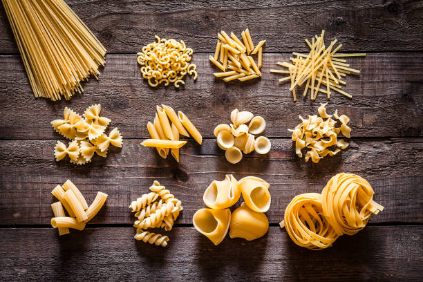Different types of Italian pasta on rustic wooden table Top view of a rustic wooden table with several heaps of Italian pasta types. The types of pasta included are spaghetti, orecchiette, conchiglie, rigatoni, fusilli, bow tie pasta, penne and tagliatelle. Predominant colors are yellow and brown. DSRL studio photo taken with Canon EOS 5D Mk II and Canon EF 100mm f/2.8L Macro IS USM bow tie pasta stock pictures, royalty-free photos & images