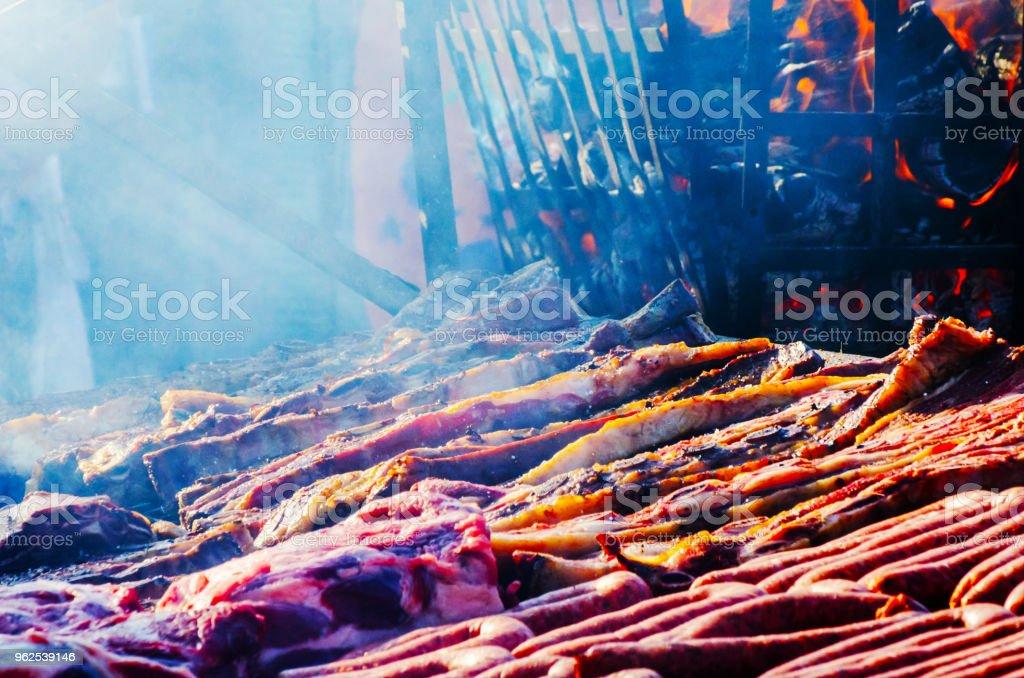 diferentes tipos de carnes e enchidos empilhados sobre uma grelha grande enquanto cozinha - Foto de stock de Almoço royalty-free