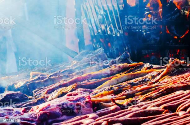 Foto de Diferentes Tipos De Carnes E Enchidos Empilhados Sobre Uma Grelha Grande Enquanto Cozinha e mais fotos de stock de Almoço