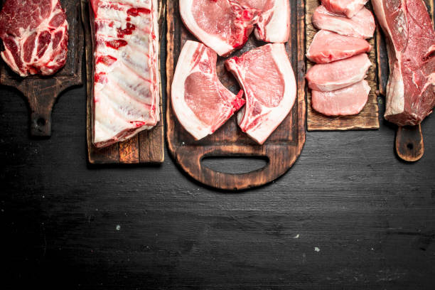 verschillende soorten rauwe varkensvlees en rundvlees. - vleesdelen stockfoto's en -beelden