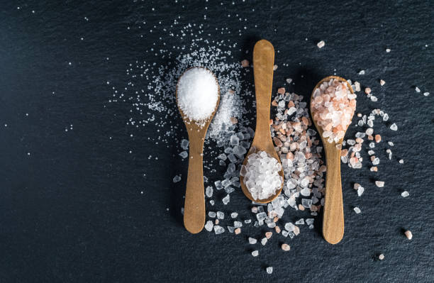 Different types of salt. Top view on three wooden spoons Different types of salt. Sea, Himalayan and kitchen salt. Top view on three wooden spoons on black background salt stock pictures, royalty-free photos & images