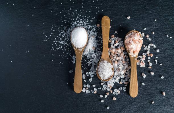 diferentes tipos de sal. vista superior en tres cucharas de madera - salado fotografías e imágenes de stock