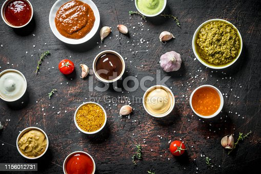 Different types of sauces. On dark rustic background