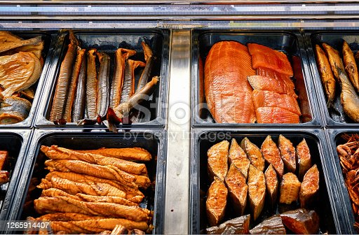 Different types of smoked fish for sale in a stand.