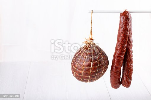Different types of smoked salami sausages on white. Copy space.