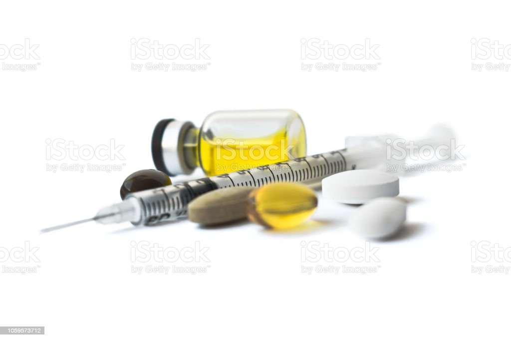 Different types of tablets, empty syringe needle, yellow liquid in ampoule,  arranged abstract