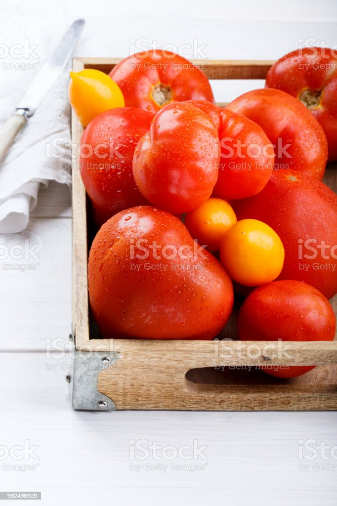 Different varieties of tomatoes on a wooden tray. Colorful red and yellow fresh ripe tomatoes - Royalty-free Agriculture Stock Photo